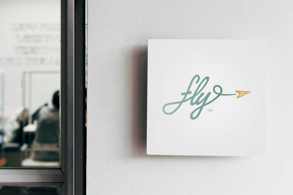 fly! logo mounted on a wall sign in an office