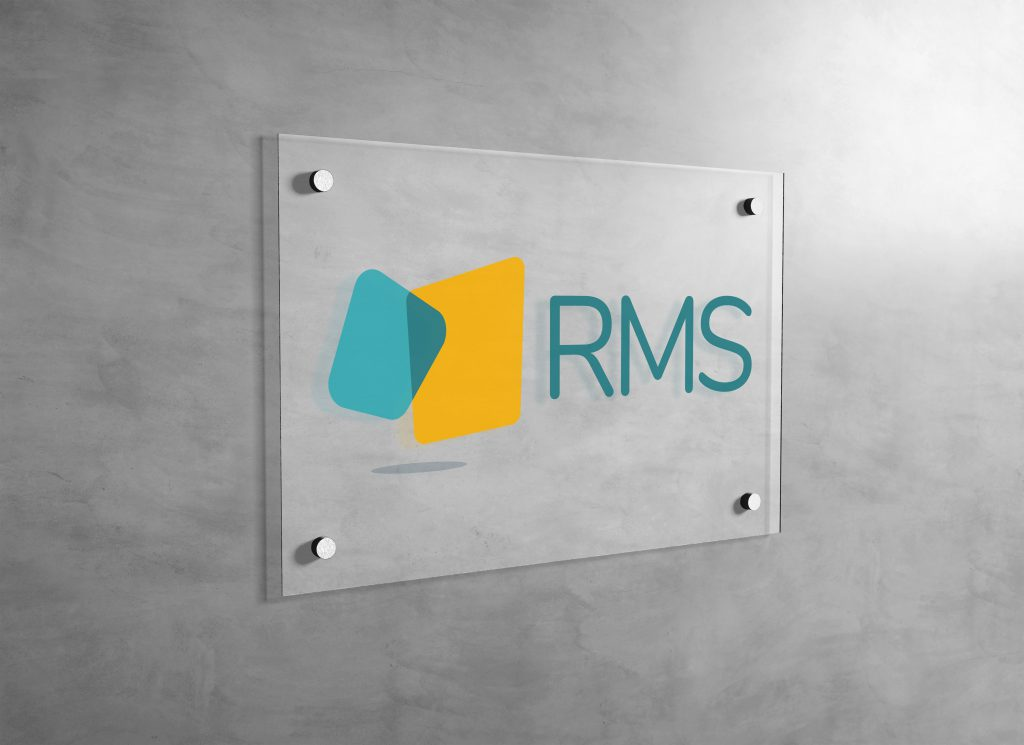 RMS logo printed on a clear plexiglass wall sign and mounted in an office