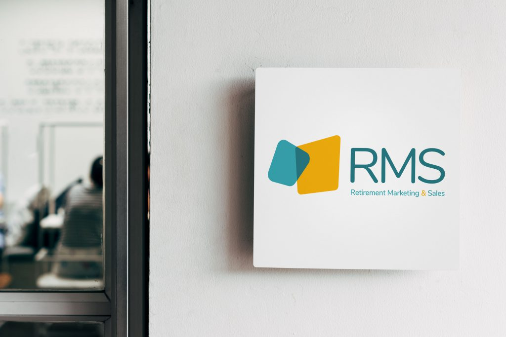 RMS logo printed on a white wall sign and displayed next to an office door