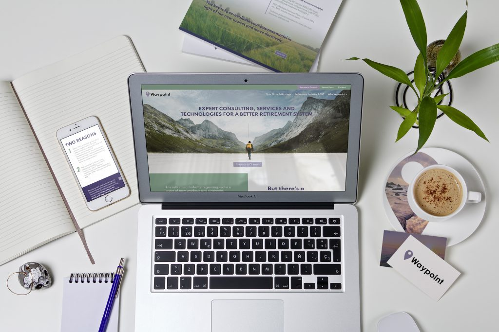 Waypoint website on a laptop surrounded by other items which also have Waypoint brand designs